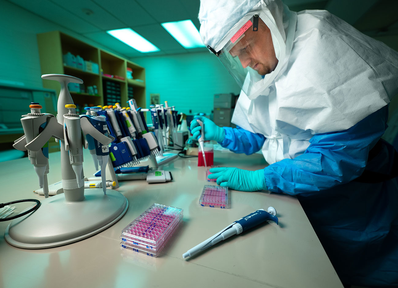 a virologist pipets a solution for coronavirus testing