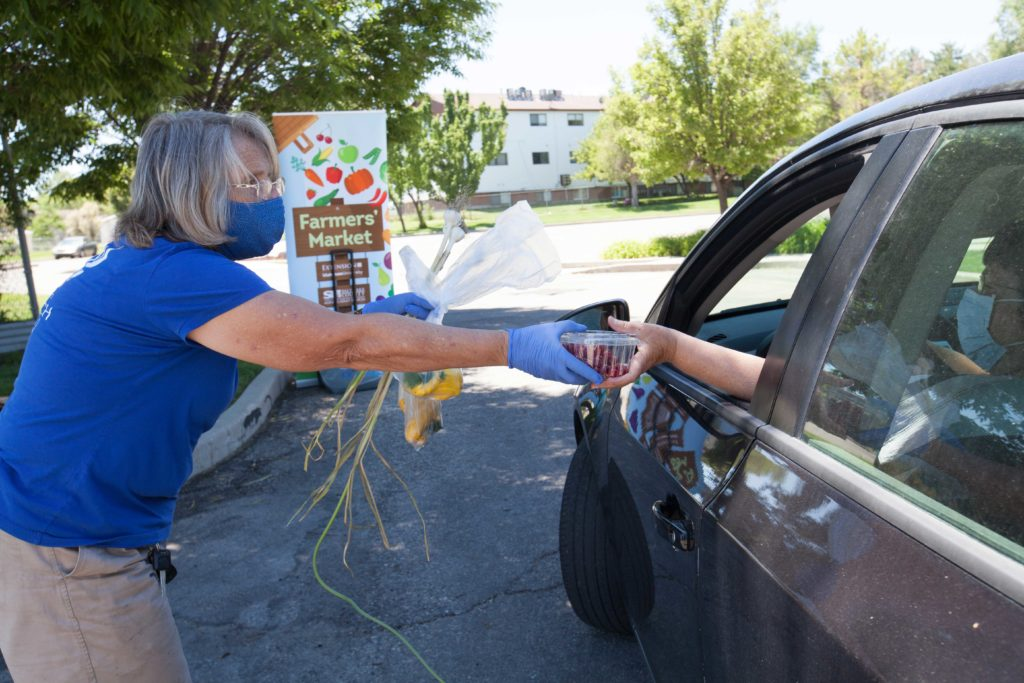 a woman wearing a surgical mask and gloves hands produce to a woman in a car