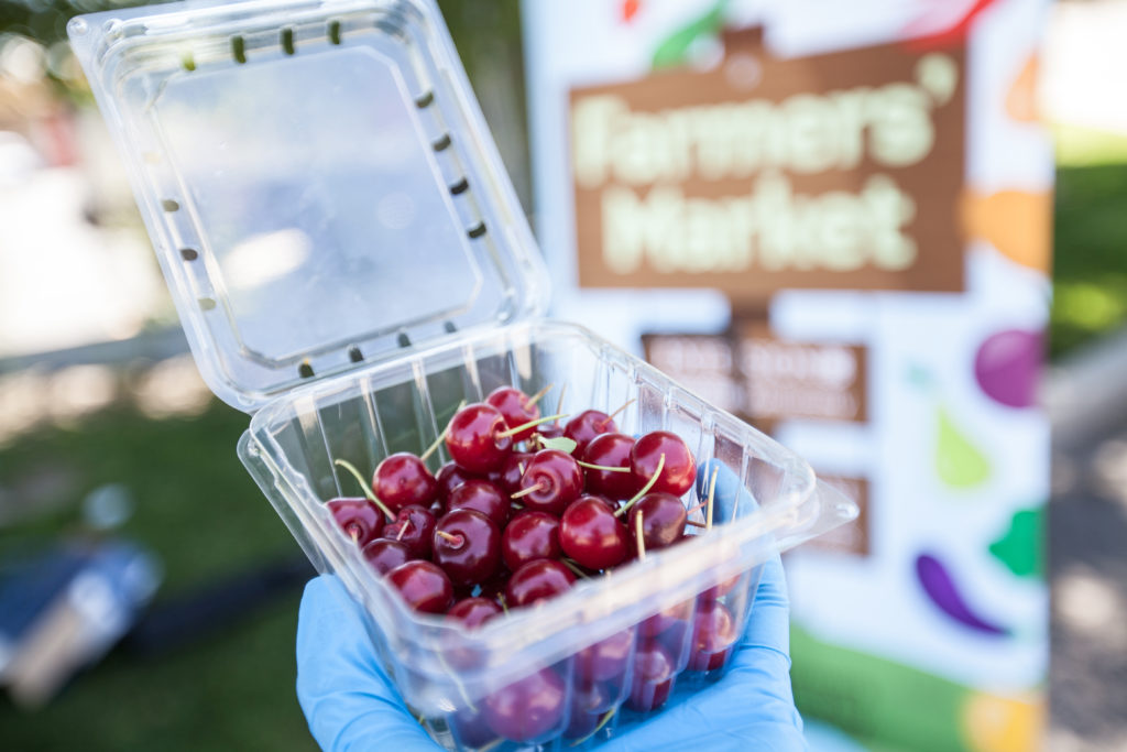 a small plastic container of red cherries