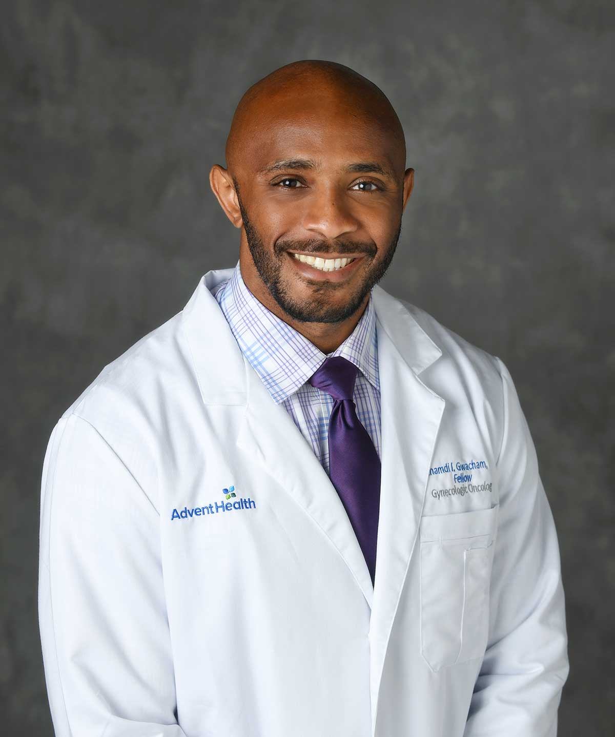 a bearded young doctor in a white coat smiles