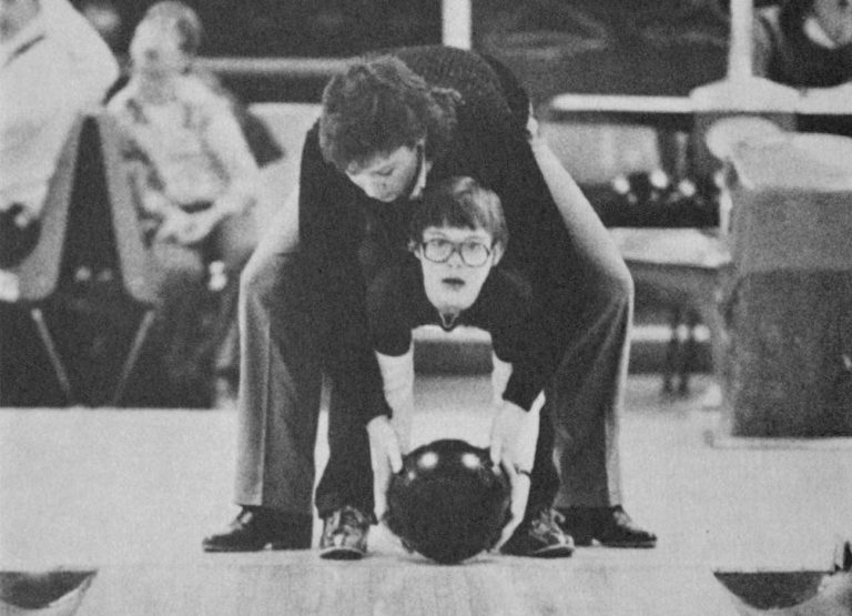 a black and white image of a USU student helping a child with special needs bowl