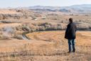 A man stands on a deserted hillside with dried grass and steam from hot springs in the background.