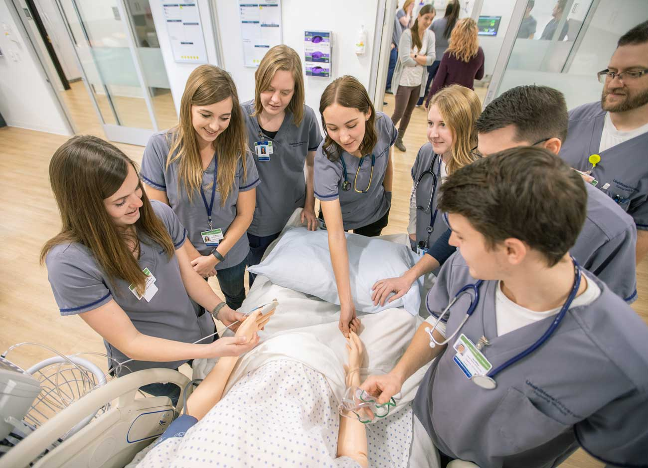 students gather around a mannequin during ther