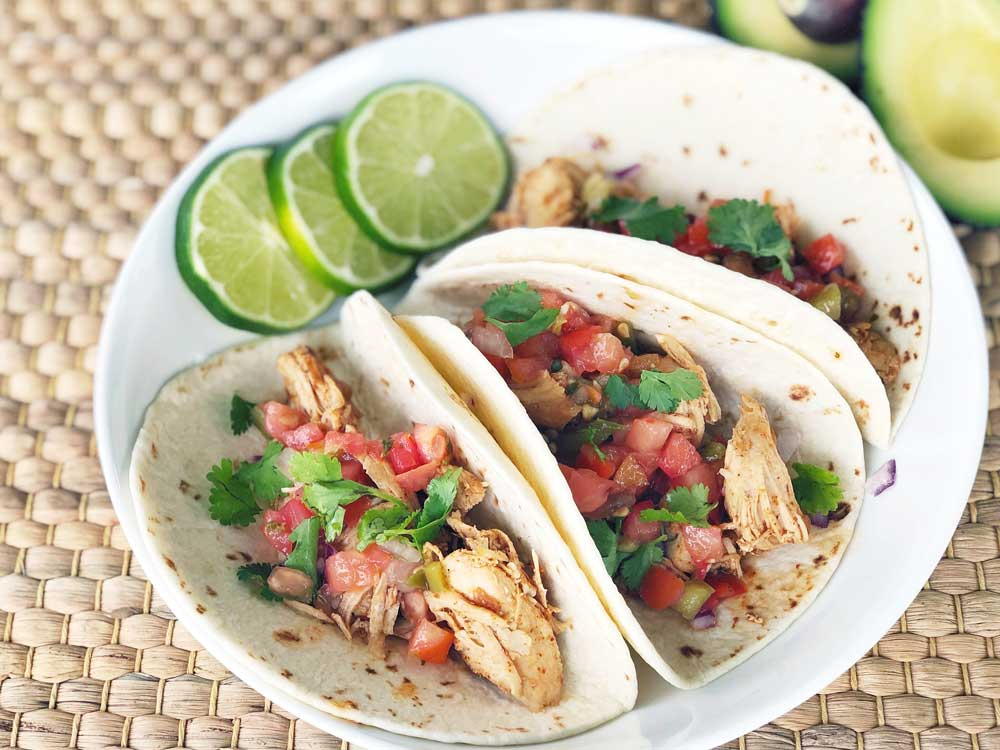 chicken tacos with salsa and lime in a bowl