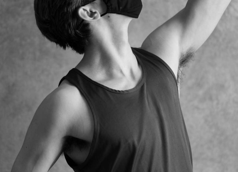 a male ballerina wears a cloth mask in class during the covid-19 pandemic