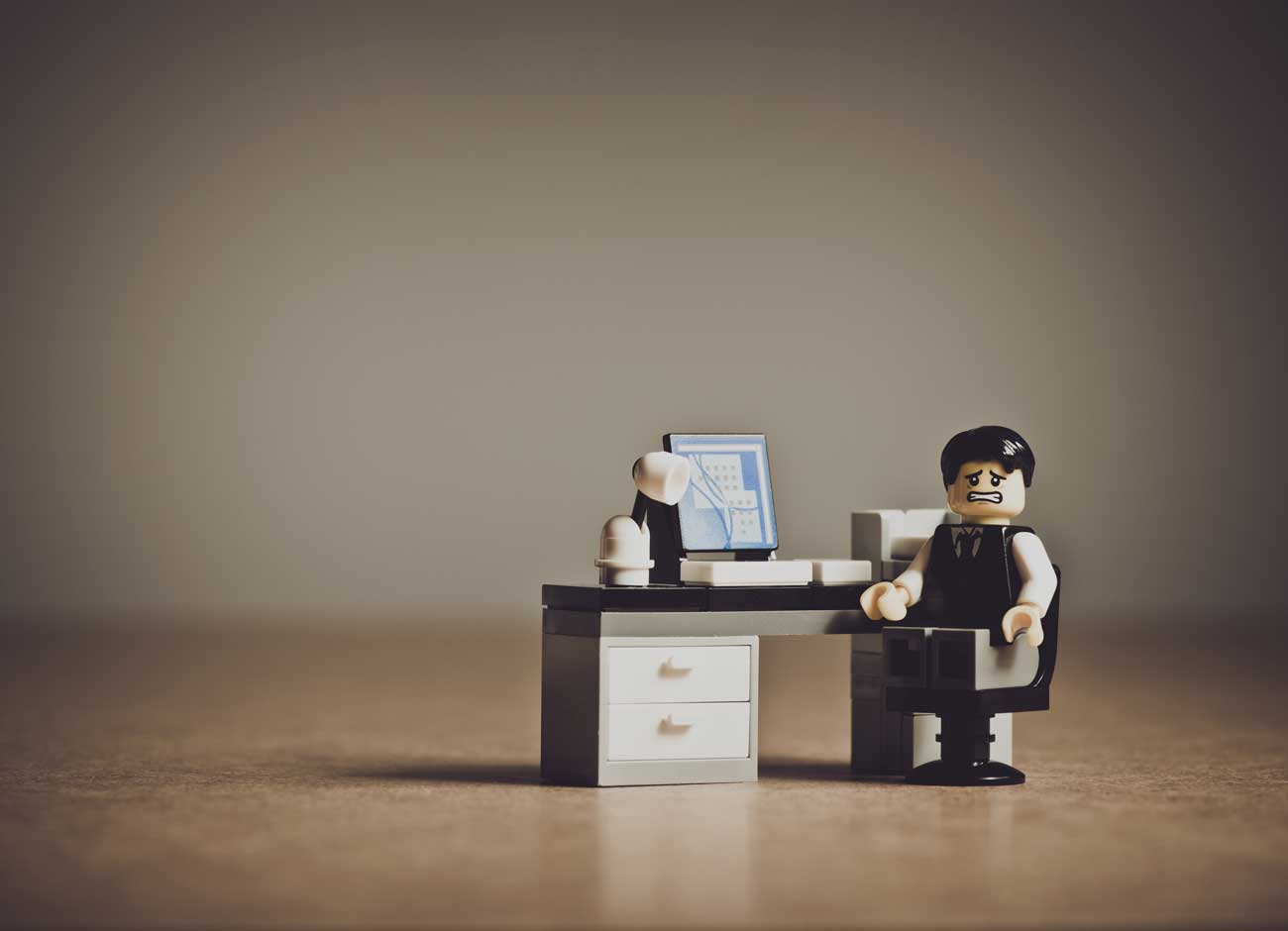 a photo illustration of a LEGO man sitting at a desk looking stressed