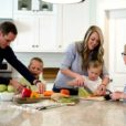 a family of five including two parents and three little boys prepares dinner in the kitchen