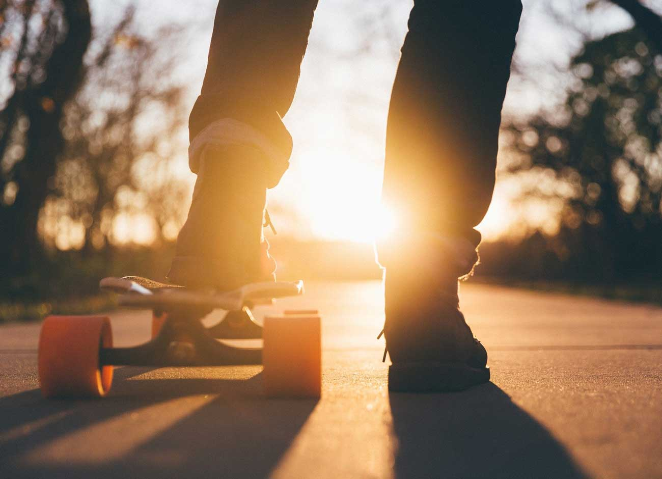 close up image of a teens feet on a skateboard riding into the sunset