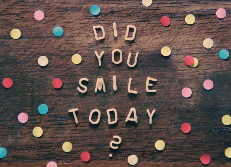 a table with a question written wooden letters Did you smile today? surrounded by confetti
