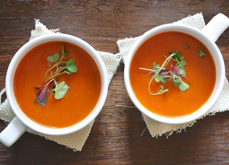 two cups of tomato soup in white bowls