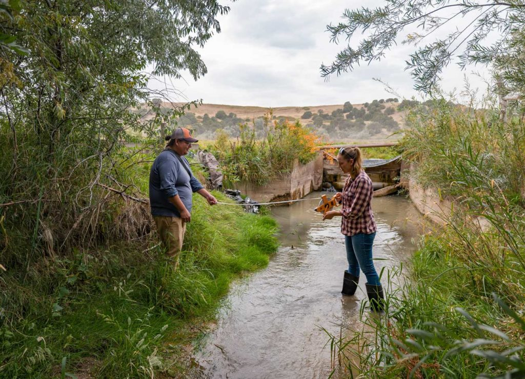 two students hold a measuring tape across a narrow stream
