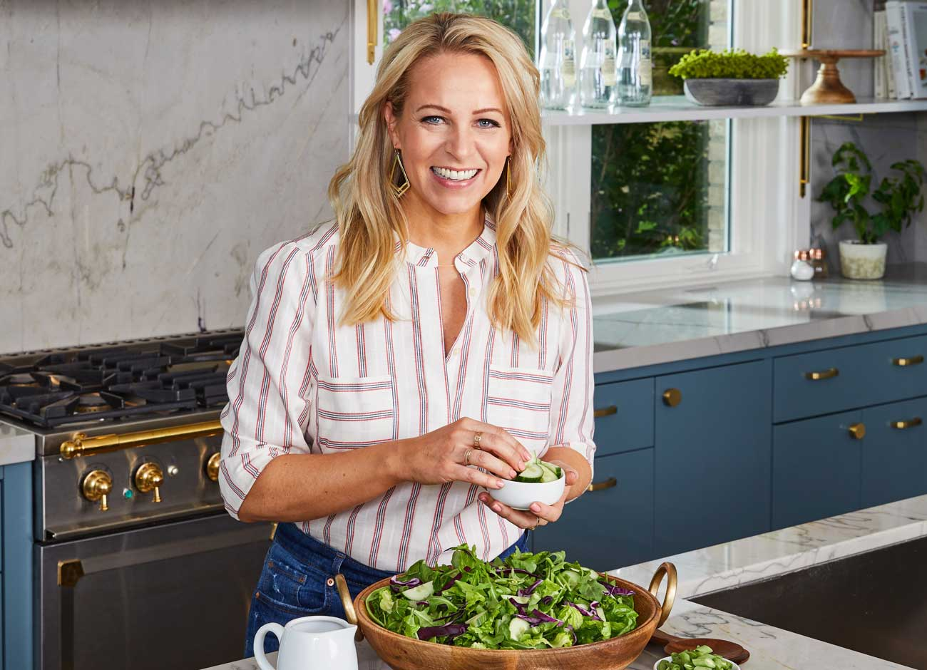 a blonde woman makes a salad in a sunny kitchen