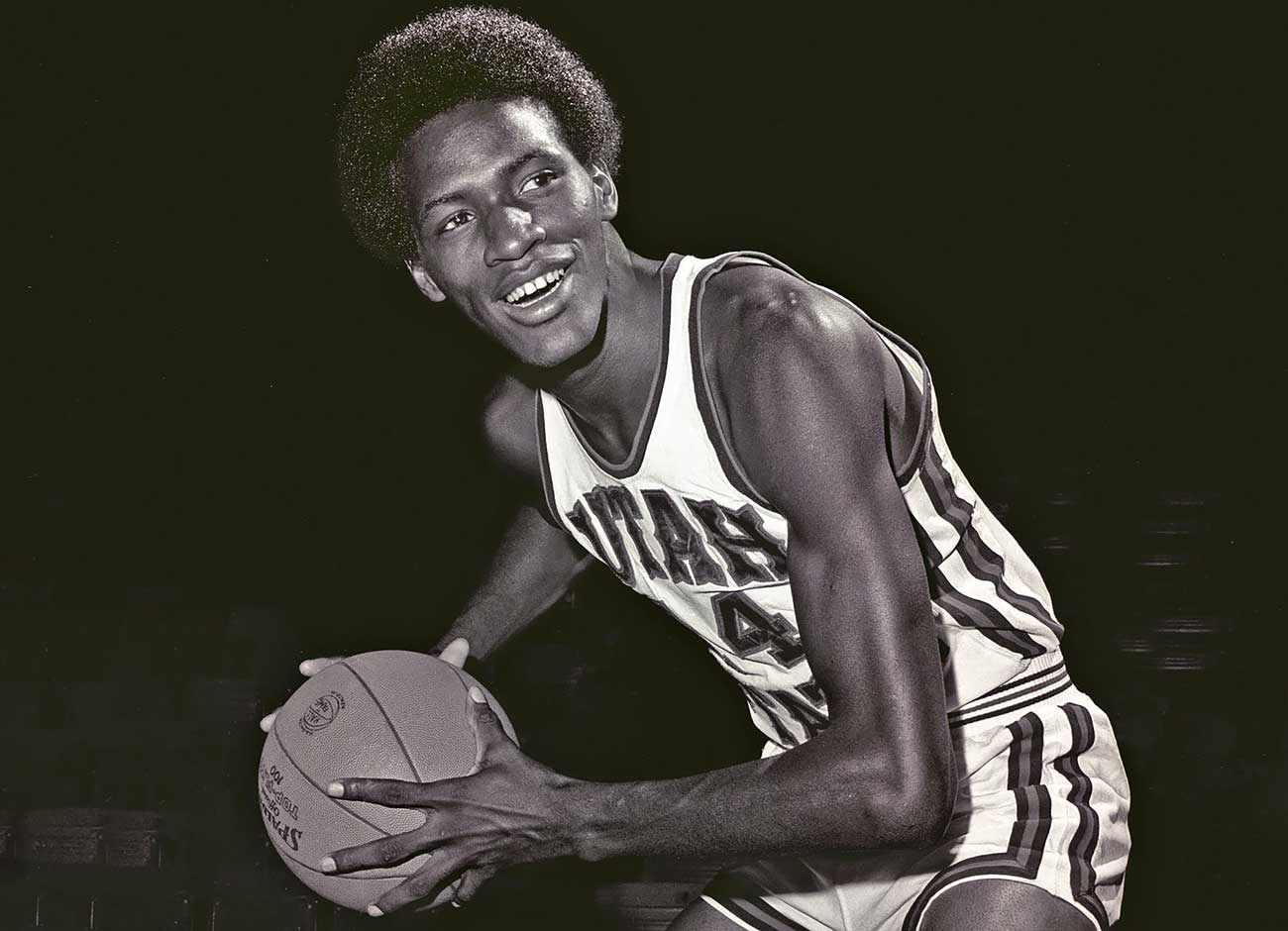 a young Black basketball player holds a ball dressed in his uniform