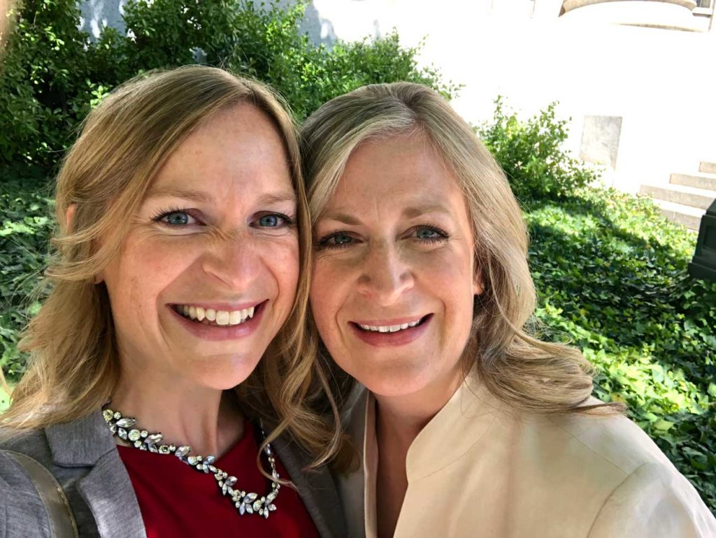 two blonde sisters smile into the camera, framed by green bushes and sunlight