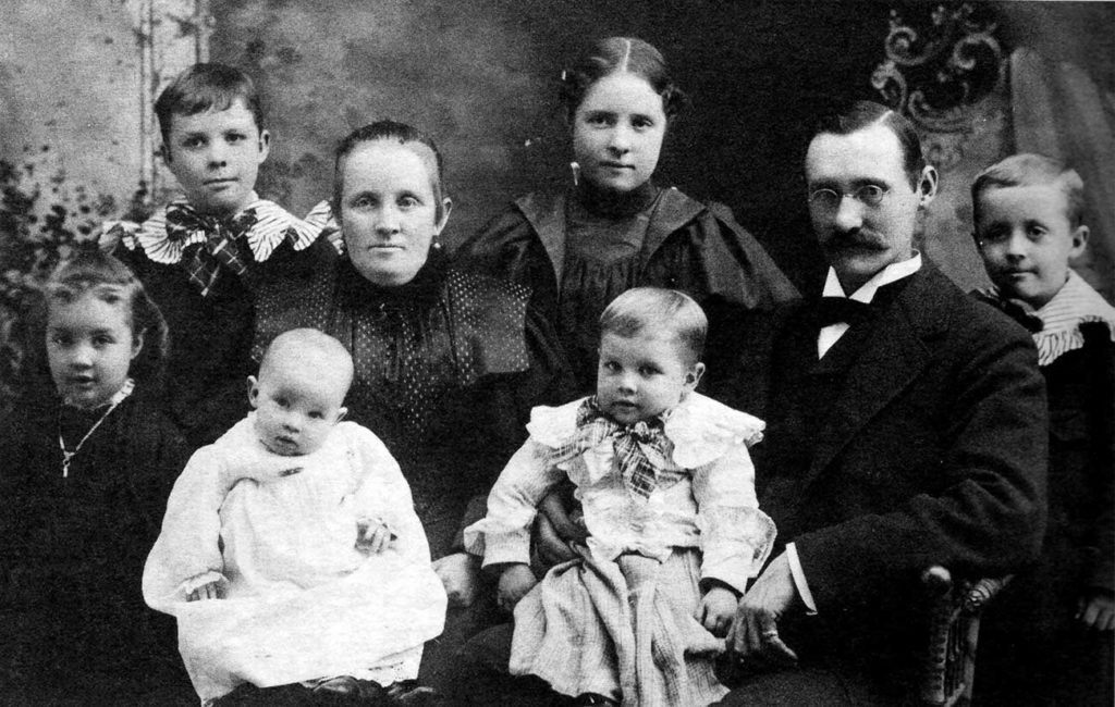 A family of 8 is photographed in 1987, none smiling in the way that would become common later.