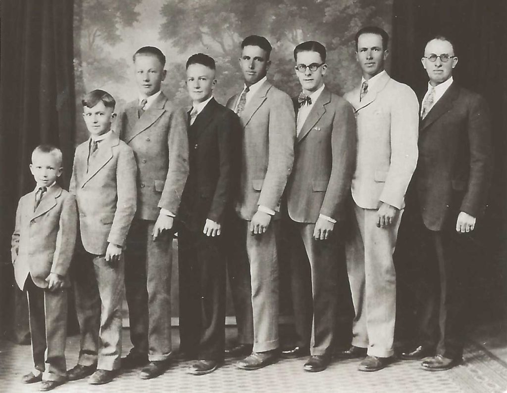 a row of 6 brothers wearing suits are lined up from youngest to oldest stand alongside their father