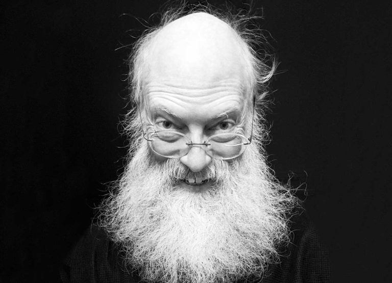 a black and white image of a 52 year old man smiling and wearing glasses. He has a long wispy white beard
