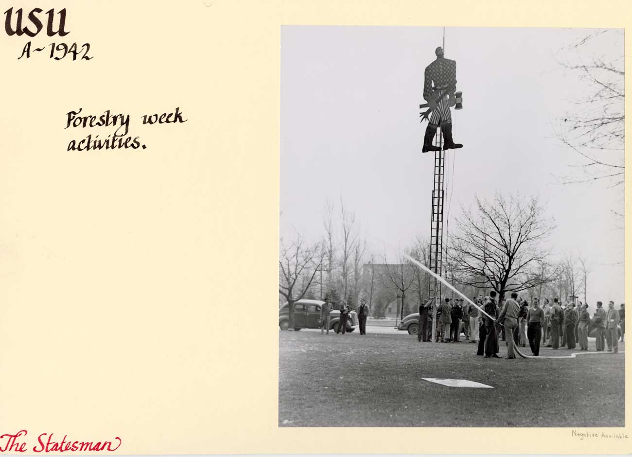 A black and white image from 1942 of a wooden Paul Bunyan statue atop a ladder. A group of men is using a firehose to keep people away while they figure out how to get Bunyan down.