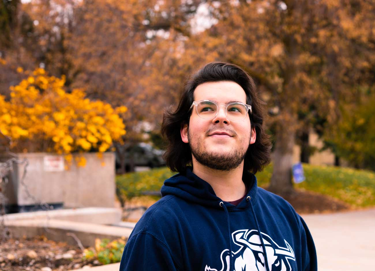 a smiling young man wears an Aggie sweatshirt and looks up at the sky with fall colors behind him