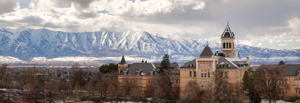 a panoramic image of Old Main with snowy mountain peaks of the Wellsvilles looming behind