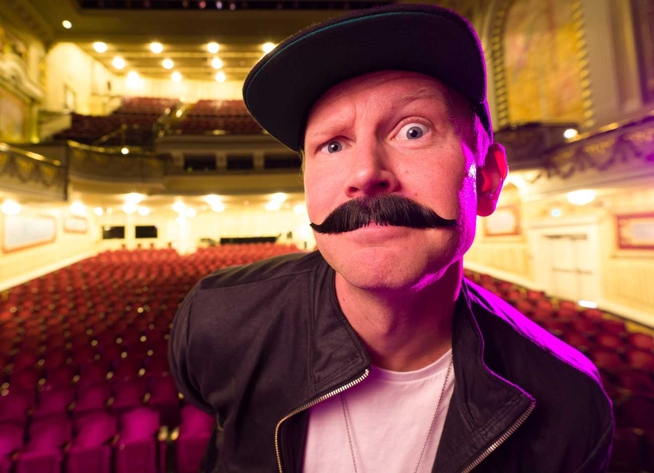 a man sits in an empty theater. he is wearing a fake mustache and amused expression