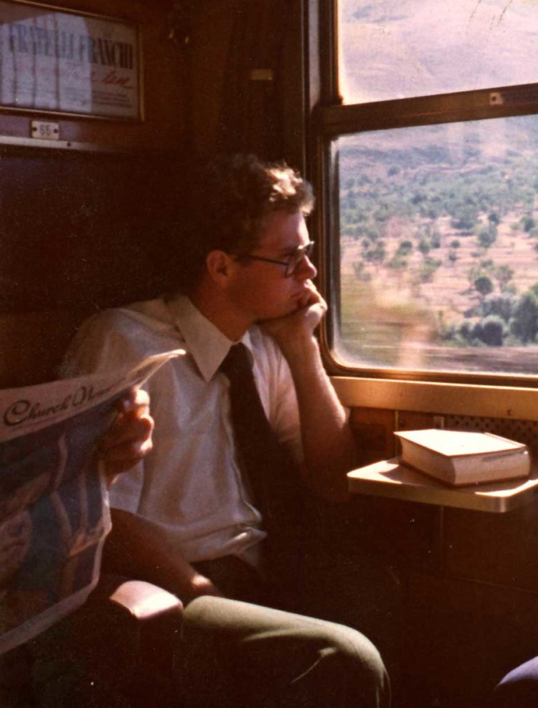 a young Mormon man sits on a train watching the scenery pass by. He is wearing a white button up shirt and black tie. His chin rests on his palm.