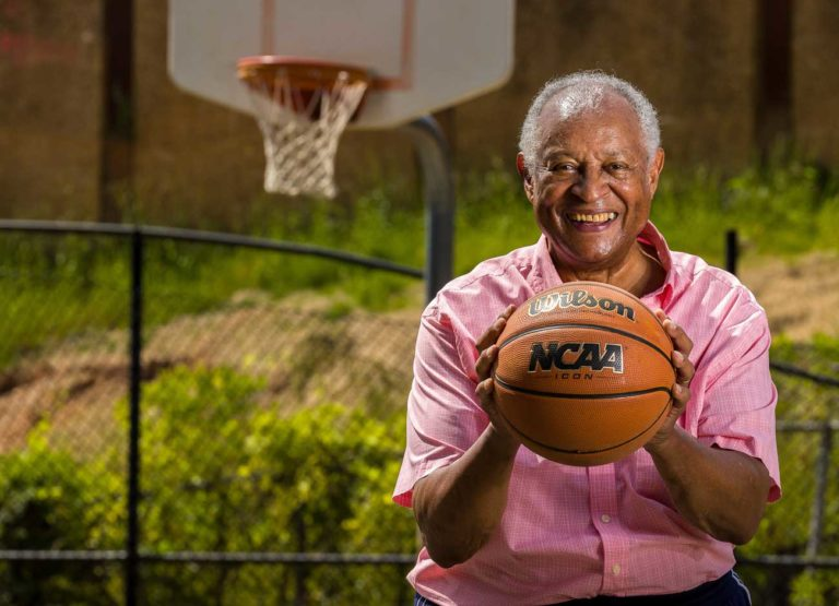 An older African American man holds a basketball. He is smiling and standing on a basketball court.