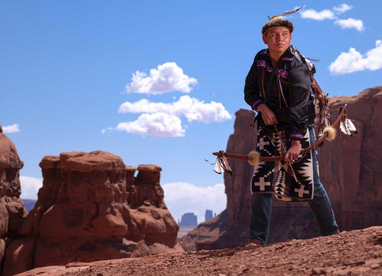 a young man in traditional Navajo dress stands on a sandstone rock and holding a bow and arrow with the backdrop of Monument Valley Utah