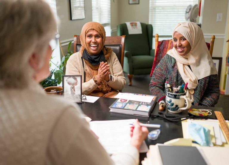 two women sit in an office smiling while talking to another woman across a table. The two women are of African descent and wearing head scarves. A pile of paperwork sits on the desk.