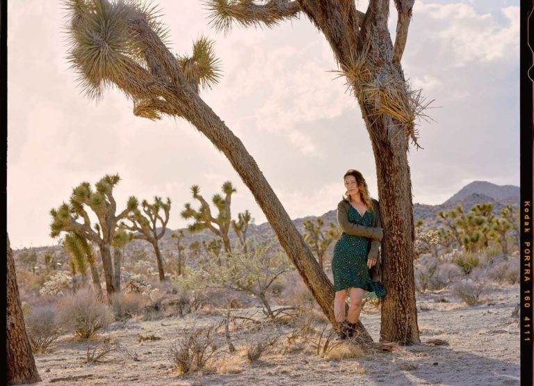 a woman in a windblown green dress and sweater leans against a Joshua tree in the desert. The sky is a pale pink color.