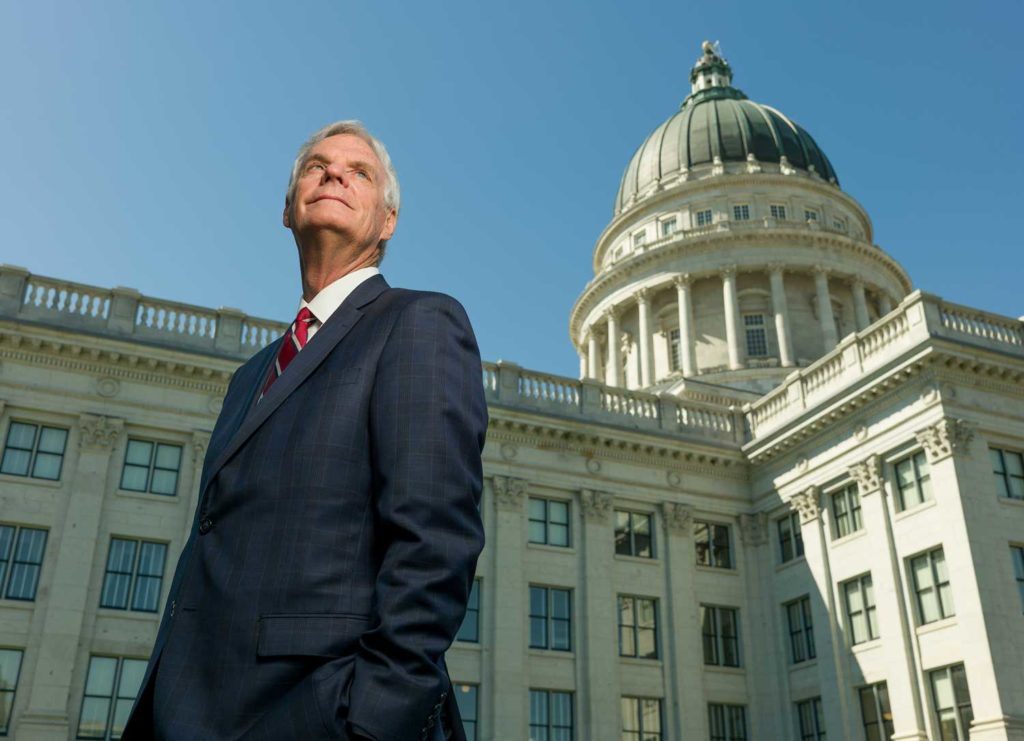 Brent Hill, a slender gray haired politician, stands with his hands in his pockets looking towards the skyline in front of the Utah Capitol building.
