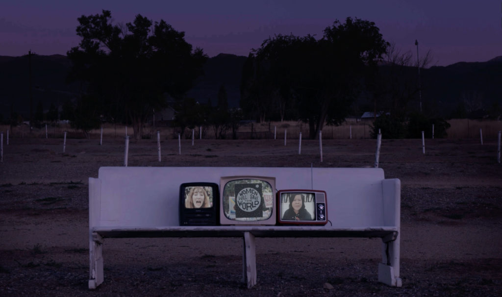 """Three television screens are lit and resting on an old white church pew. The bench is outside in an empty parking lot. Trees and mountains are outlined in the background. The middle television reads """"Women will save the world."""""""