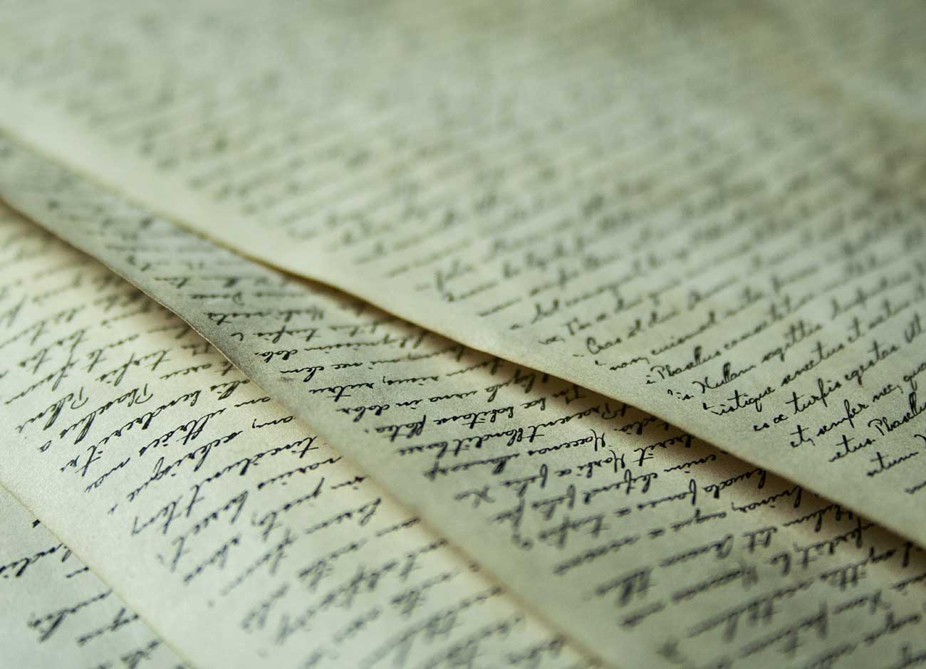 a stack of parchment paper with cursive writing