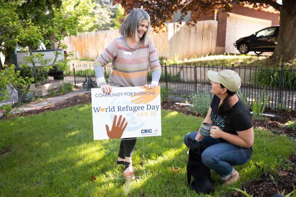 a smiling gray haired woman pushes a lawn sign into her yard that reads 'Community for Everyone: World Refugee Day June 20 CRIC'