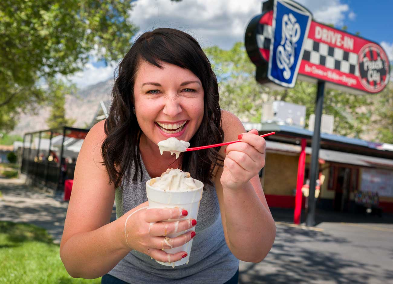 a woman with black hair grins while holding a melting milkshake and eating it with a spoon. the drips fall down her hands. she stands in front of a drive in.