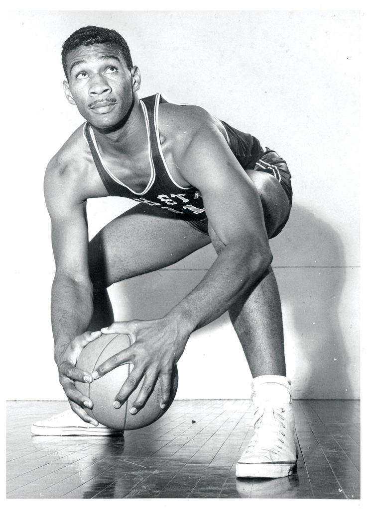 An African American basketball player squats holding a basketball. His eyes gaze upward as if sizing up his next shot.