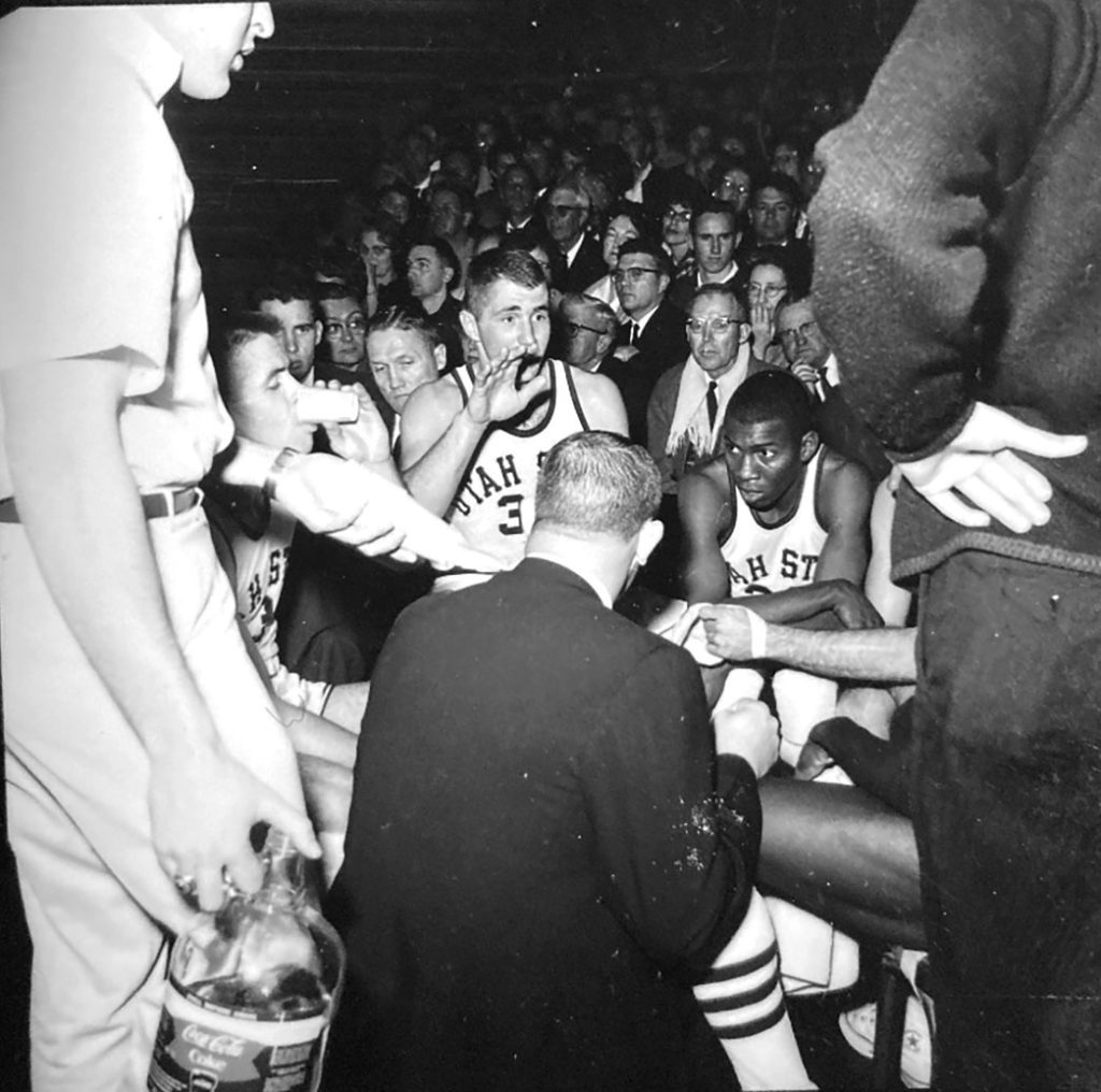 Two men in basketball uniforms - one White, the other African American, sit in a huddle during a game. A crowd looks on behind them.