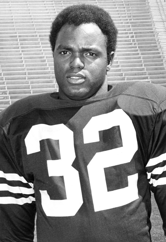 An African American man wearing the 32 football uniform looks off to the side during practice.