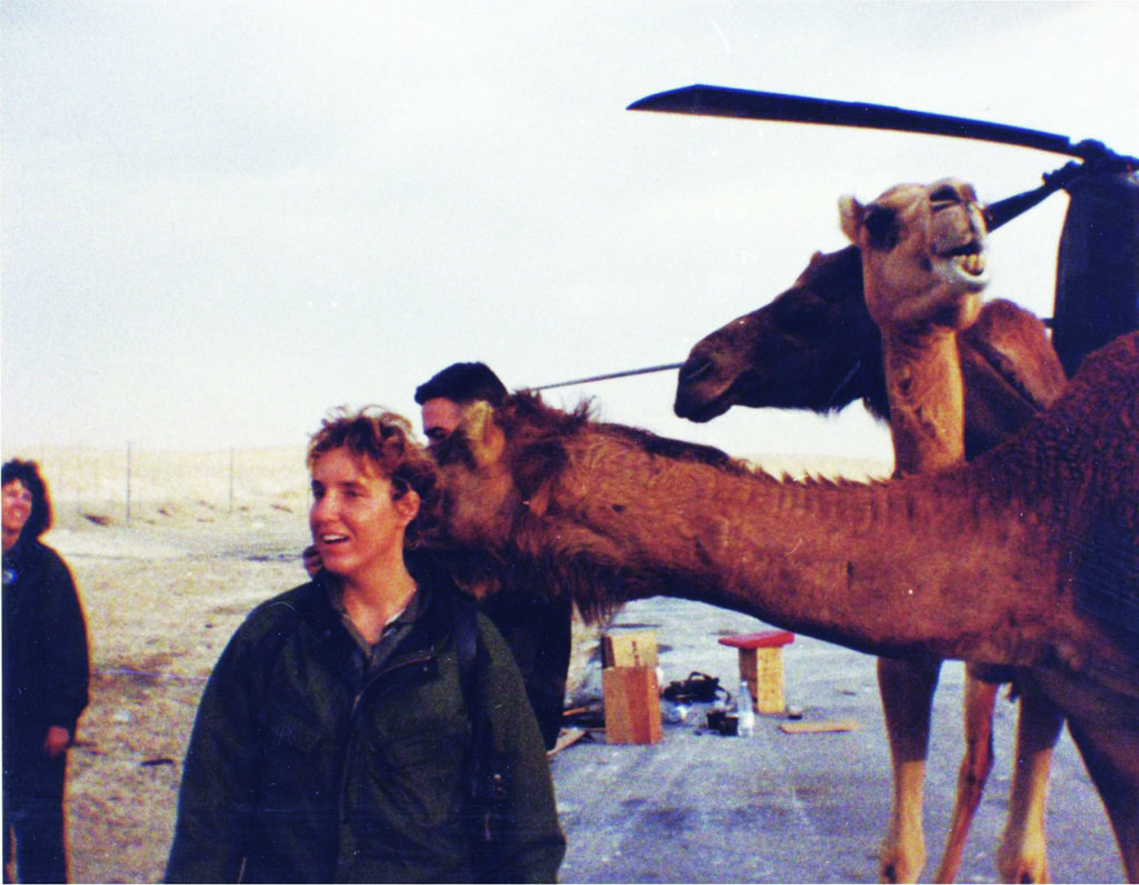 a woman in Army fatigues stands in front of three camels during the Gulf War. She is not looking at the camera.