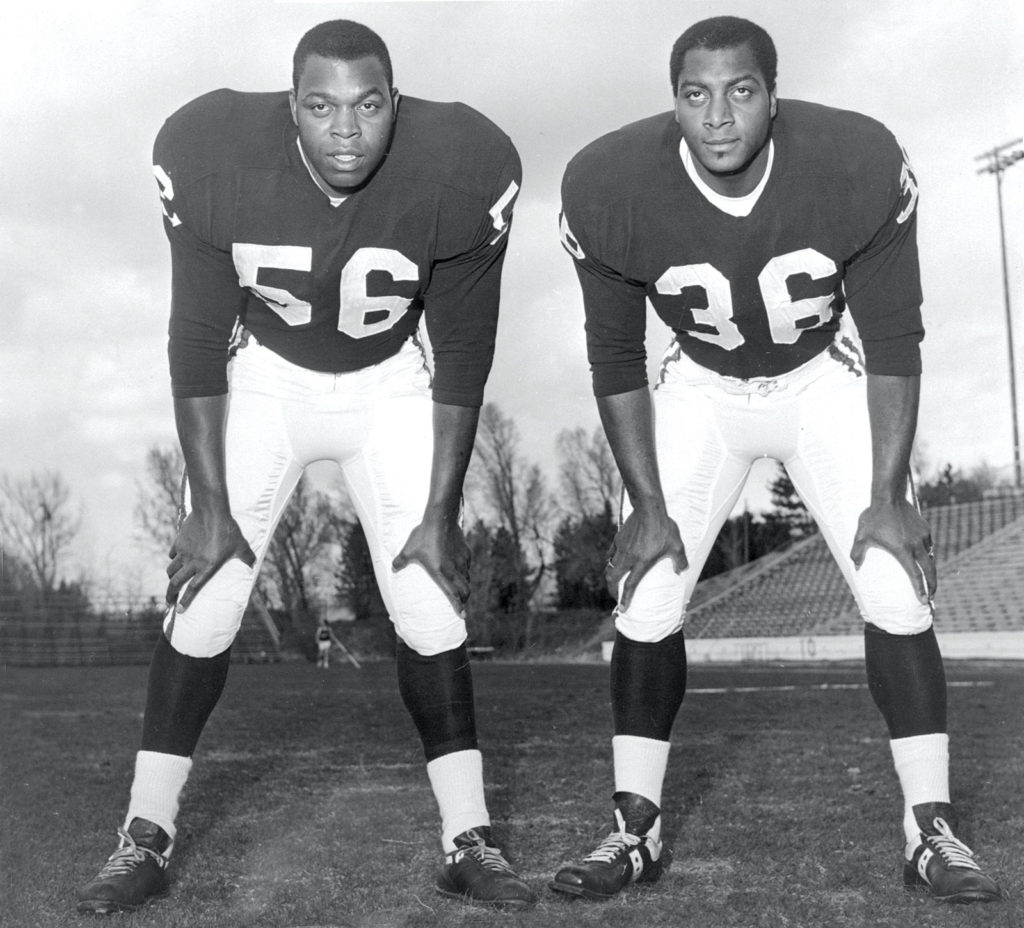 Two African American men in football uniforms stare into the distance. Both have their hands on their knees.