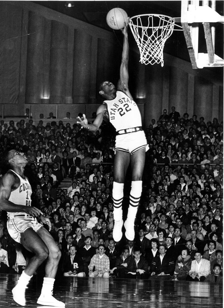 An African American basketball player wearing the 22 uniform is captured mid-air holding a basketball. His hand grazes the rim.
