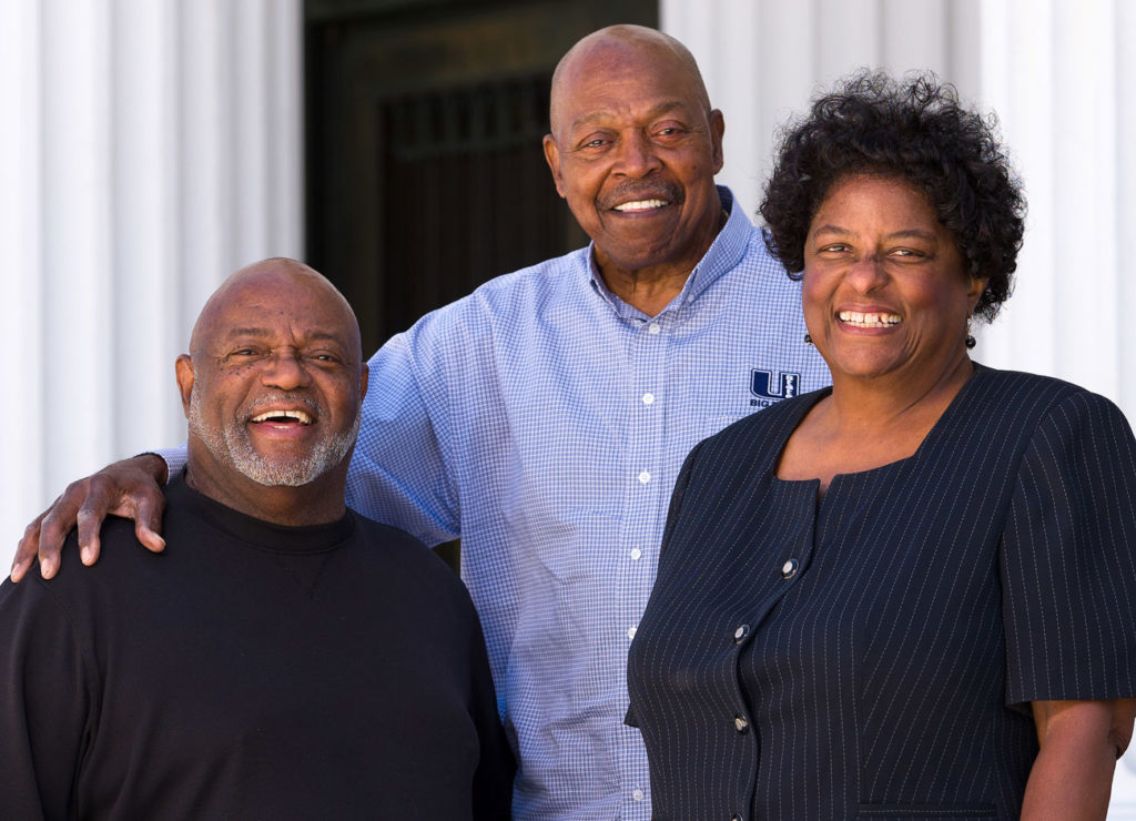 three African American friends, two men and one woman, stand together smiling. Two Roman columns are in the background.
