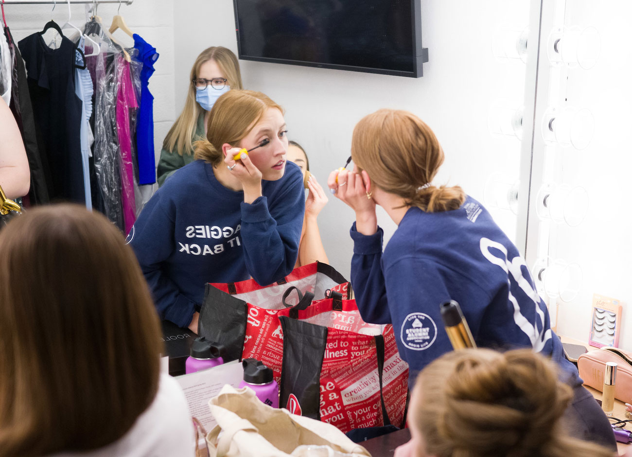 a young woman leans toward a large mirror as she puts on her makeup. a rack of evening dresses is in the background. she is wearing an Aggie t-shirt.
