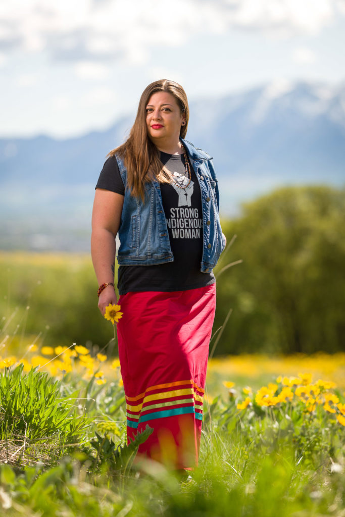"""A young Native American woman wearing a t-shirt with the words """"Strong Indigenous Woman"""" and a red skirt with rainbow stripes stands in a field of golden flowers. A mountain is in the distance."""
