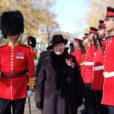 a woman dressed in a black coat and hat stands between guardsmen clad in red uniforms during a Canadian ceremony.