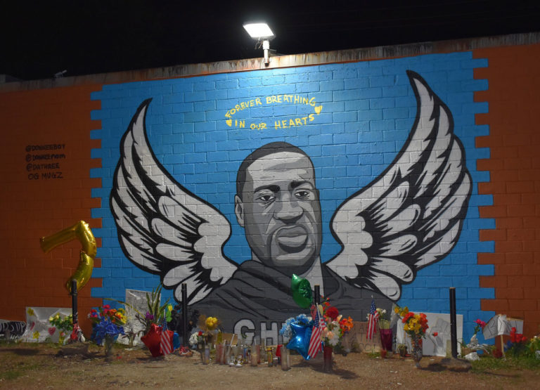 a memorial tribute to George Floyd. The mural depicts Floyd with angel wings and a halo painted on a brick wall. Flowers, stuffed animals. and signs from protests are on the ground. The mural is in Houston.