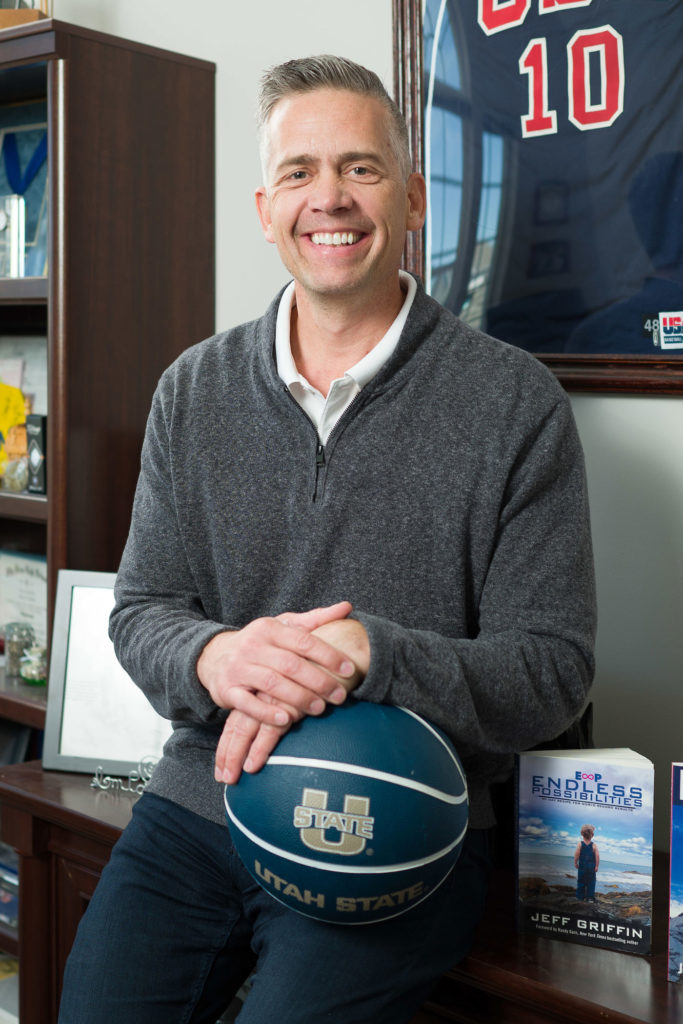 """a White man in a gray zip up sweater leans against a desk. He is smiling and holding a Utah State basketball in his hands. To the left of his left elbow is a book reading """"endless possibilities"""" which he wrote."""