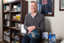 """a man with salt and pepper hair leans against a bookshelf holding a blue Utah State basketball. His two books """"endless possibilities"""" and """"I'mpossible"""" are perched below the ball."""