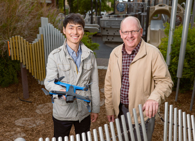 two professors stand in a playground, one holds a drone. Both are smiling. In the background are climbing structures, slides, and musical structures children activate through play.