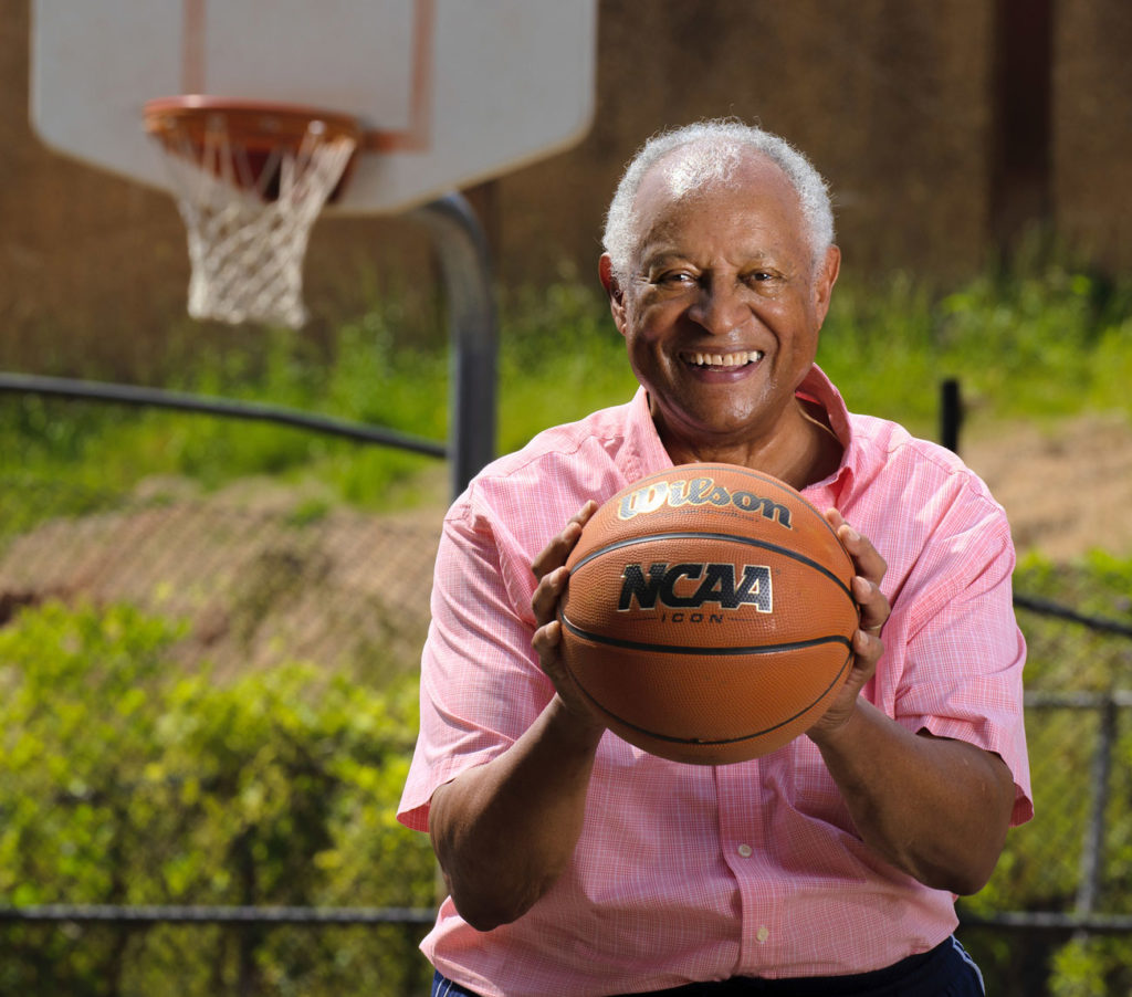 an older African American man wearing a red button up short sleeve shirt holds a basketball under a net. He is smiling.
